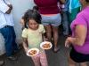 Migrantes recibiendo comida desde una pequeña cocina dentro del campamento.