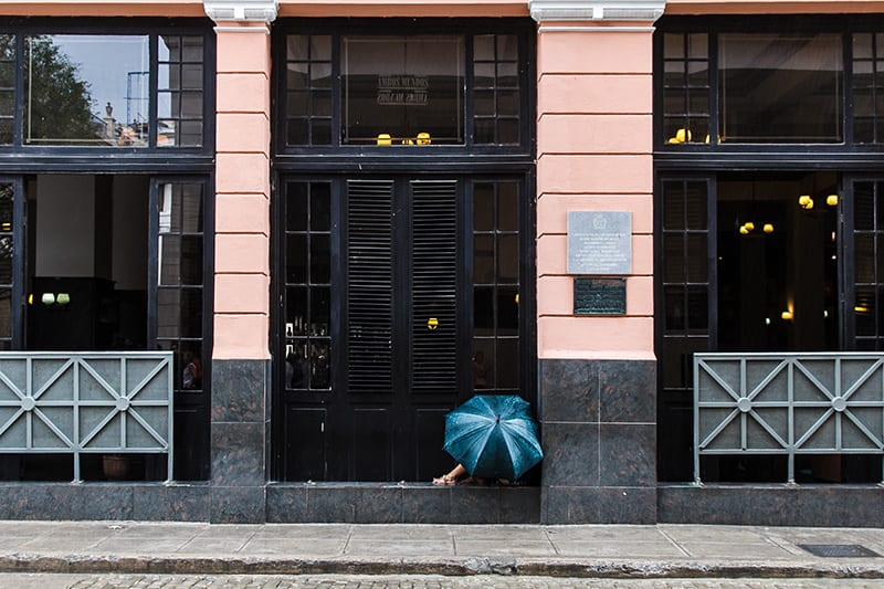Muchacha conectada a la wifi bajo la lluvia por el hotel Ambos Mundos. Foto: Juan Suarez