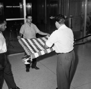 This Jan. 7, 1961 AP file photo shows unidentified U.S. embassy employees rolling up a U.S. flag as the embassy transfers American affairs to the Swiss.  On Friday a new flag will be hosited at the newly opened embassy.