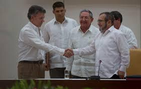 Se saludan Juan Manuel Santos y Timoleón Jimenez tras la firma de los acuerdos. Observan Raúl Castro, Bruno Rodríguez y el guardaespaldas y nieto de Raúl.  Foto: cubadbate.cu