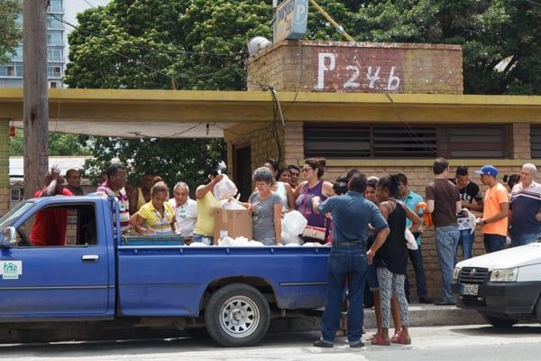 Trabajadores del Ministerio del Azúcar reciben como estímulo una jaba con carne de cerdo en una calle concurrida del Vedado Foto: Juan Suárez