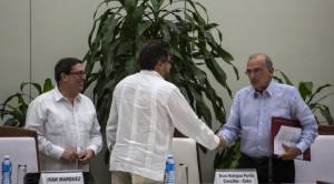 Humberto de La Calle, right, head of Colombia's government peace negotiation team shakes hands with , Ivan Marquez, chief negotiator of the Revolutionary Armed Forces of Colombia (FARC), center, as Cuba´s Foreign Minister Bruno Rodriguez, left, looks on after the signing of the latest and definitive text of the peace accord between the two sides in Havana, Cuba, Saturday, Nov. 12, 2016. (AP Photo/Desmond Boylan)